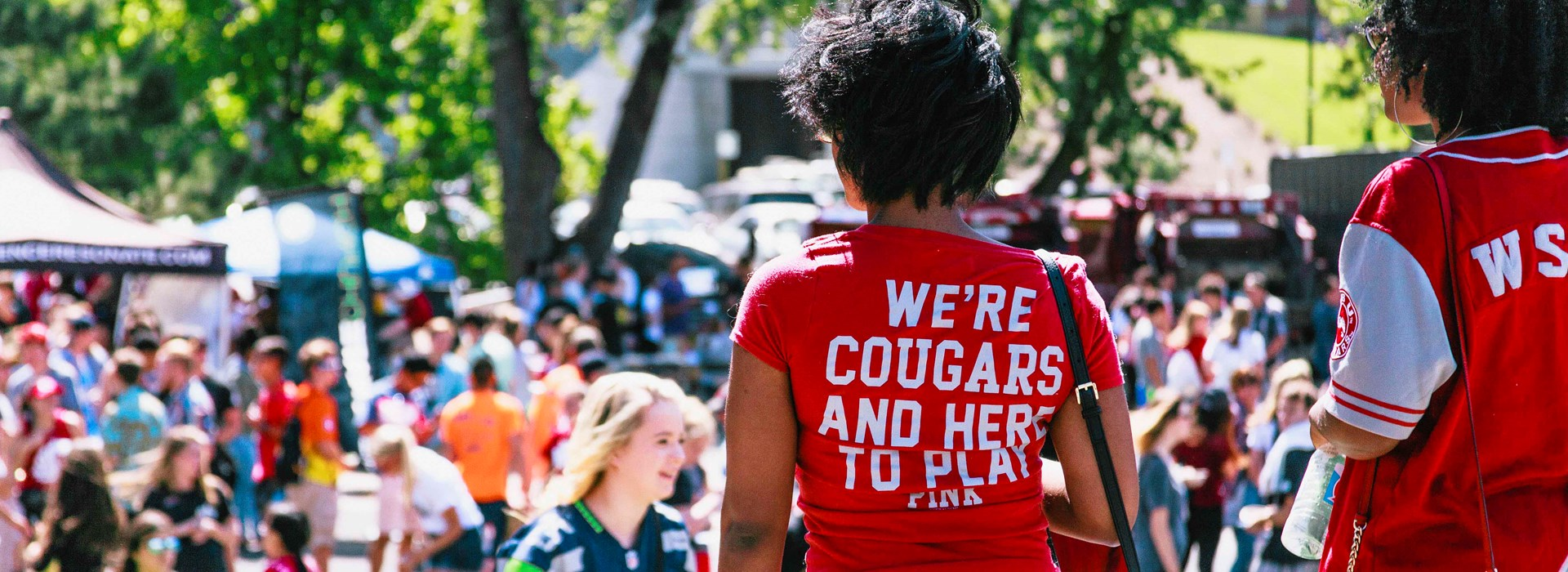 "Student wearing a shirt that says ""We're Cougars and hear to play."""