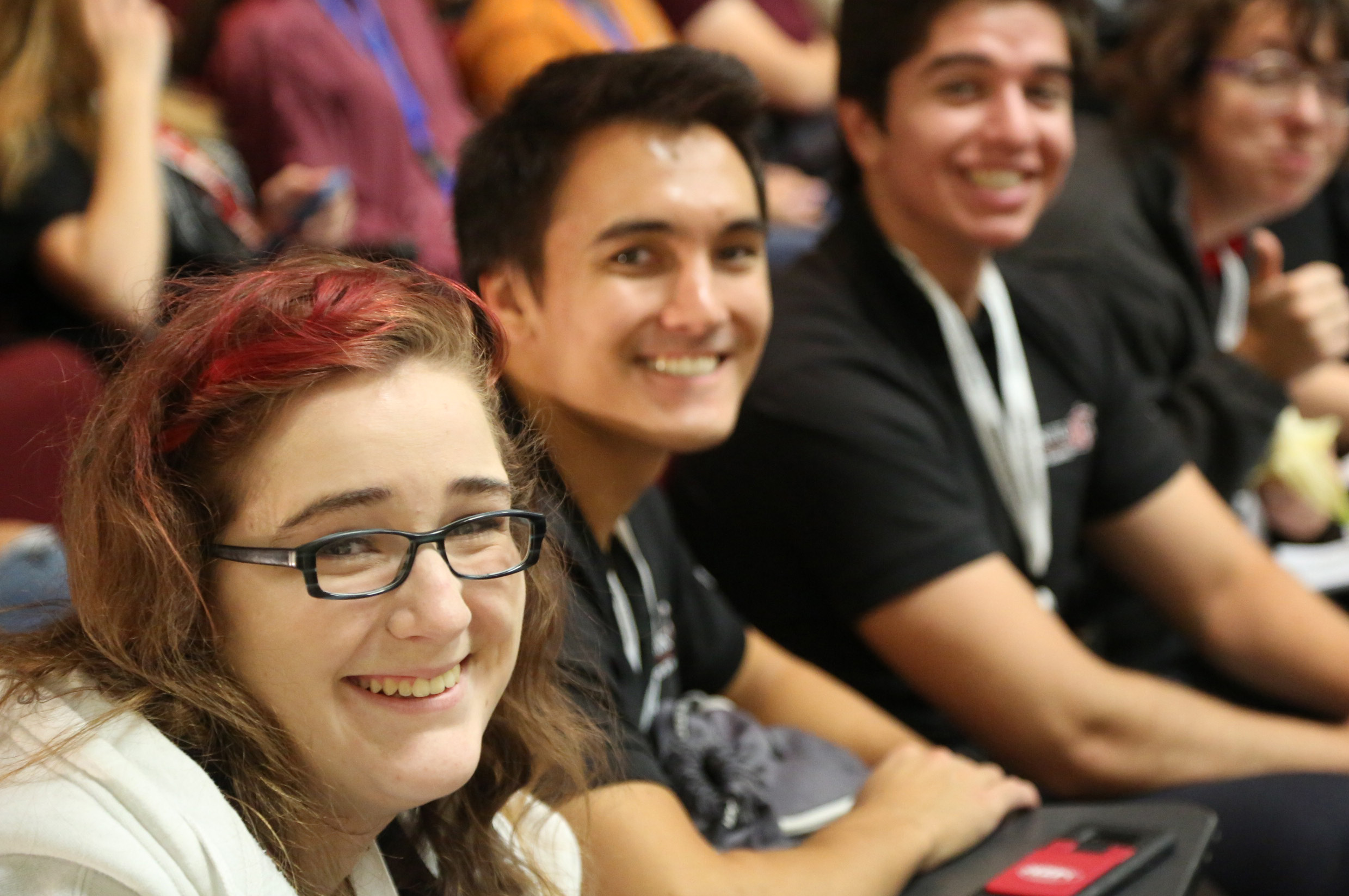Students smiling at a conference.