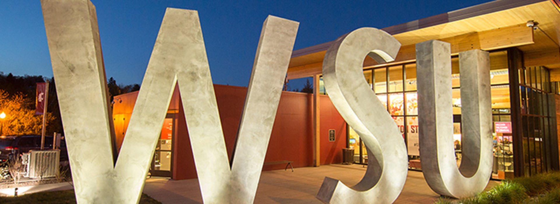 Exterior of Brelsford visitor center focused on the concrete letters that spell WSU