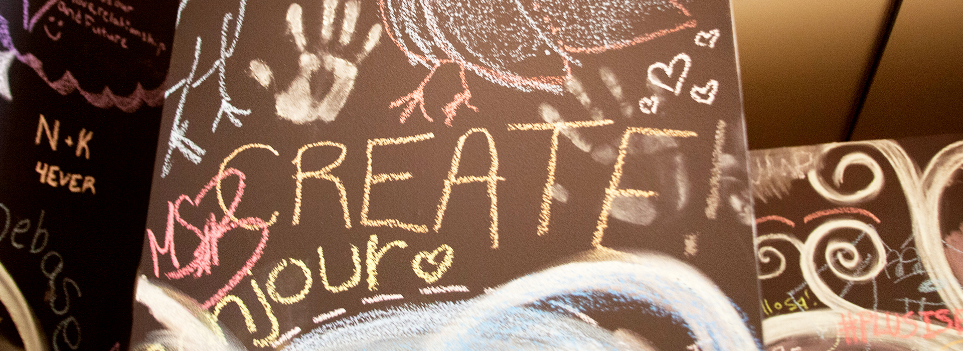 Photo of chalk art from the CUB Gallery, focus on the word create